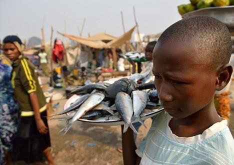 Keskiafrikkalainen poika möi kalaa Banguin lentokentän liepeille muodostuneella evakkoleirillä keskiviikkona. EU:n mahdollinen kriisinhallintaoperaatio suojelisi pakolaisia.