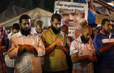 Vallasta syrjäytetyn islamistipresidentti Muhammed Mursin kannattajat rukoilivat myöhään tiistai-iltana Muslimiveljeskunnan kapinaleirissä Kairossa.