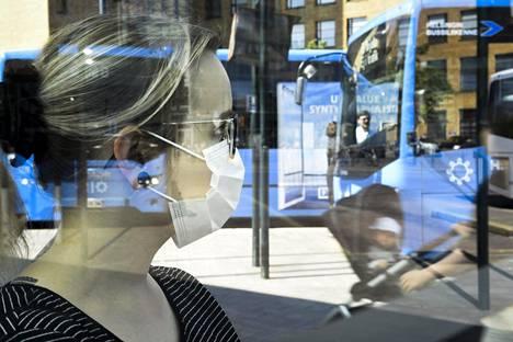 Vihreät, kokoomus, kristillisdemokraatit ja perussuomalaiset mainitsivat esimerkiksi julkiset liikennevälineet paikkoina, joita maskisuositus voisi koskea. Hengityssuojainta käyttävä nainen matkustaa bussilla Helsingissä 26. kesäkuuta.