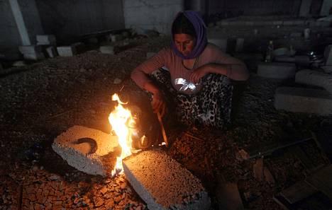 Sinjarista paennut nainen teki ruokaa keskeneräisessä rakennuksessa. Kymmenettuhannet jesidit ovat paenneet väkivaltaa vaikeisiin oloihin.