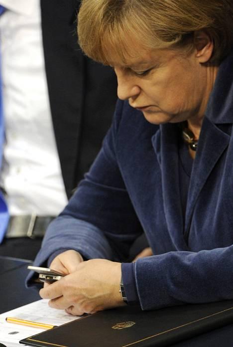 Liittokansleri Angela Merkel tutki puhelintaan lokakuussa 2011 liittopäivillä Berliinissä. Saksalaislehti Der Spiegelin mukaan Yhdysvaltojen epäillään urkkineen Merkelin puhelinta.