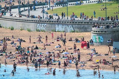 Pietarilaiset nauttivat helteestä koronaviruspandemian vuoksi suljetun 300-vuotispuiston rannalla kesäkuussa. Puisto avattiin lopulta kesäkuun viimeisenä viikonloppuna.