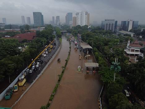 Listan kärjessä on Indonesian pääkaupunki Jakarta, jota piinaavat niin pahenevat saasteet, tulvat kuin helleaallotkin. Ilmakuva tulvivasta tiestä Jakartassa helmikuulta 2021.