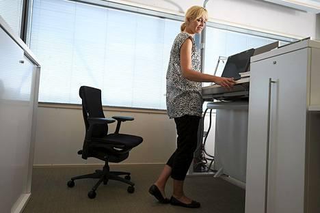 Päivi Rissanen UPM:n pääkonttorissa Helsingissä säätää pöydän korkeutta seisomatyöhön sopivaksi.