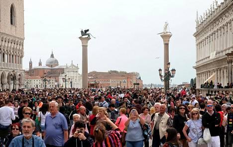 Venetsiassa vierailee vuosittain noin 25 miljoonaa turistia. Kuvassa matkailijoita Pyhän Markuksen torilla Venetsiassa huhtikuussa 2018.