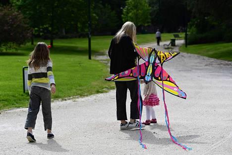 Nainen ja tytöt matkalla lennättämään leijaa Sempionen puistossa Milanossa maanantaina.