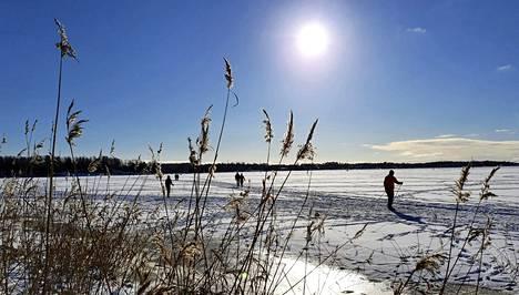 Ulkoilijoita jäällä Vanhankaupunginlahdella Helsingissä aurinkoisena laskiaissunnuntaina 14. helmikuuta 2021.
