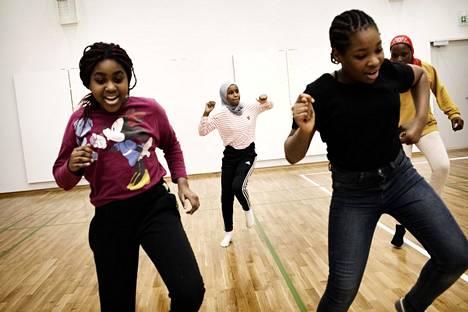 Viidesluokkalaiset Christela Ilumbe Bosange (vas.), Riham Dirie, Maeva Tara, Rokey Sabally ja kuvasta puuttuva Efua Yawson harjoittelevat tanssiesitystä.