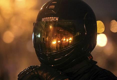 Palavien renkaiden liekit heijastuivat mieleosoittajan kypärän visiiristä Kiovassa torstaina.