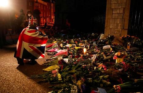 Yhdistyneen kuningaskunnan lippuun sonnustautunut surija otti kukkamerestä kuvia perjantai-iltana Windsorin linnan ulkopuolella.
