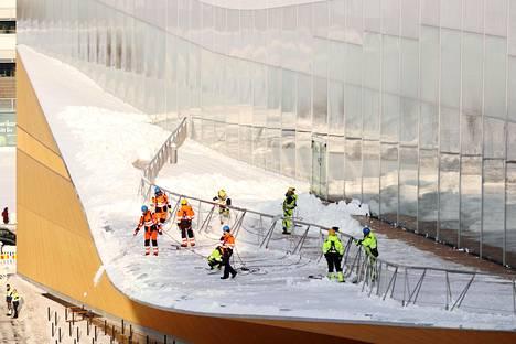 Keskustakirjasto Oodin lipan päällä työskenteli torstaina ainakin yhdeksän lumenpudottajaa.