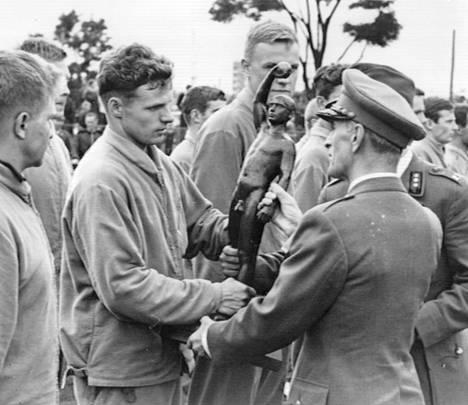 """Porin Prikaati voitti jälleen ylivoimaisesti puolustusvoimain yleisurheilumestaruuskilpailujen joukkueosastojen välisen kilpailun. Kuvassa kenraali Adolf Ehrnrooth luovuttamassa """"Voittaja""""-patsasta parhaalle varuskunnalle."""