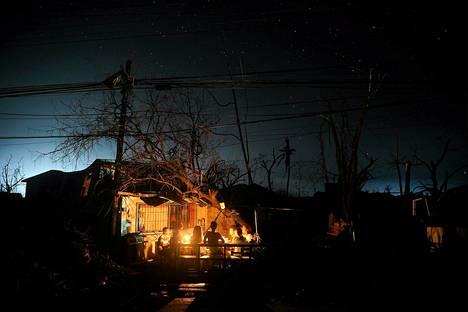 Taifuunista selviytyneet söivät illallista talonsa terassilla Taclobanissa.