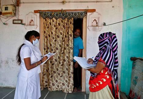 Intialaiset terveysviranomaiset keräsivät asukkailta henkilötietoja rokotusohjelman aikataulutusta varten Ahmedabadin laitamilla maanantaina.