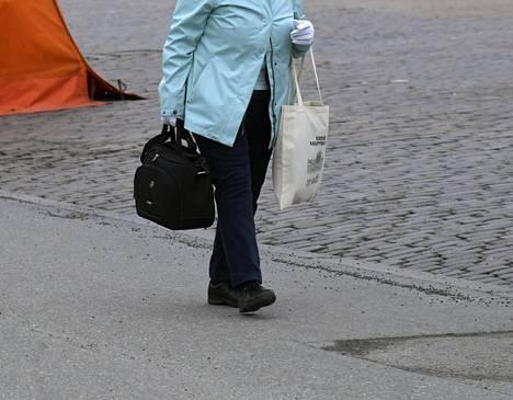 Seniorikansalainen Helsingin Kauppatorilla keskiviikkona 18. maaliskuuta 2020. Hallitus velvoittaa yli 70-vuotiaita pysymään erillään kontakteista muiden ihmisten kanssa mahdollisuuksien mukaan.