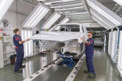 Antti Hannonen ja Kirsi Urpanen tarkastivat valmisteilla olevan auton maalipintaa helmikuussa Valmet Automotiven tehtaalla Uudessakaupungissa.