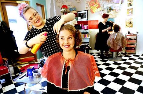 """""""Pitää kuunnella hiusta, minnepäin se lähtee menemään"""", sanoo kampaaja Kati Talikka ja kertoo nauraen olevansa hiuskuiskaaja. Pinkissä Paplarissa tehdään vintagetyylejä, mutta myös vaikkapa ekojuttuja. Asiakas Katja Ojala on tullut kampaamoon viettämään äidin kuusikymppisiä siskonsa ja äitinsä kanssa: haussa on kampaukset 50-luvun tyyliin."""
