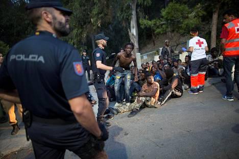 Poliisi valvoi Marokon puolelta luvattomasti rajan ylittäneitä ja teon yhteydessä kiinniotettuja afrikkalaisia siirtolaisia Espanjan Ceutassa tiistaina.