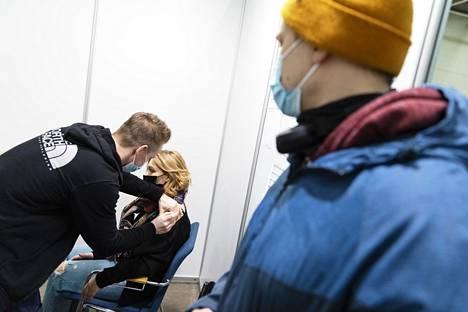 Hoivakodissa työskentelevät Olga Malmi, 43 (kesk.) ja Ruslan Ramazanov, 37 (oik.) saivat Pfizer-Biontechin rokotteen Messukeskuksen rokotuspisteellä Helsingissä tiistaina.