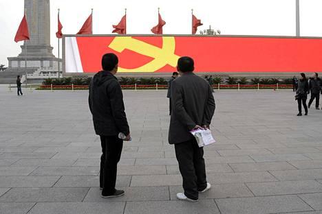 Kiinalaismiehet katsoivat elektronisella taululla näkyvää Kiinan kommunistisen puolueen tunnusta Taivaallisen rauhan aukiolla Pekingissä torstaina.