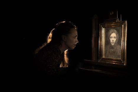 Taidehistorioitsija Hanna-Reetta Schreck katsoo Ellen Thesleffin omakuvaa Kansallisgallerian varastossa.
