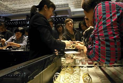 Koruliikkeen myyjä esitteli asiakkaille rannerenkaita Hongkongissa viime huhtikuussa.