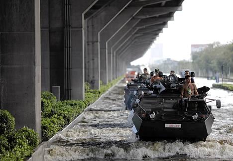 Sotilaat ajavat tulvivalla kadulla Bangokissa keskiviikkona.