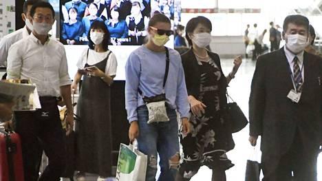 Tsimanouskajan (keskellä) oli määrä lentää keskiviikkona Japanista suoraan Puolaan, mutta hänen lentonsa vaihdettiin lopulta Itävaltaan.