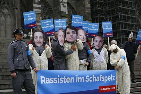Oikeistopopulismia vastustavia mielenosoittajat naamareineen Kölnin tuomiokirkon edessä naamareissa.