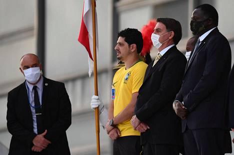 Brasilian presidentti Jair Bolsonaro (toinen oikealta) suostui pitämään kasvosuojusta perjantaina tervehtiessään tukijoitaan presidentin palatsin edustalla.