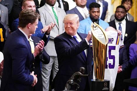 Joe Burrow (vas.) antoi Donald Trumpille joukkueensa pelipaidan numerolla 45 varustettuna.