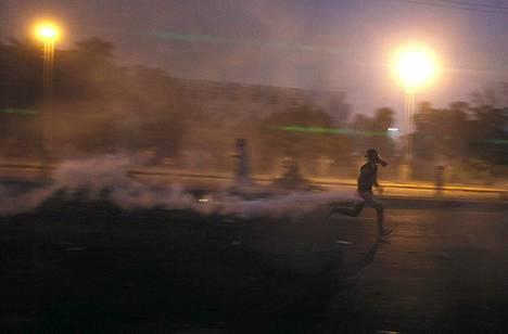 Muhammed Mursin kannattaja kuljetti poliisin alunperin ampumaa kyynelkaasukanisteria Kairossa lauantaina.