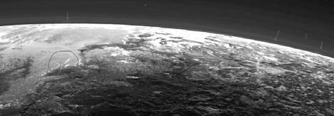 Lähelle kuvan vasempaa reunaa on planeetatutkija ympyröinyt Pluton kaasukehästä mahdollisia vaaleita, pitkulaisia pilviä.