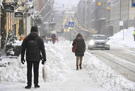 Jalankulkijoita lumisella Aleksanterinkadulla Helsingissä torstaina.