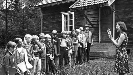 He käyvät koulua myös heinäkuussa ja mielellään. Kivelän torpan pihamaalle Sysmässä on kokoontunut lapsia Tampereelta, Forssasta, Asikkalasta, Tammelasta. Heidän opettajansa Veera Tietti selittää esperanton kielellä mitä nyt pitäisi tehdä.