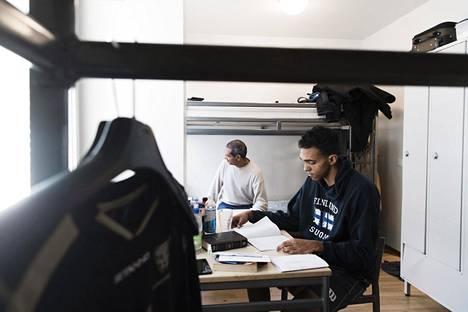 Abraham Pineda opiskelee suomea isänsä Alexis Pinedan kanssa heidän huoneessaan.