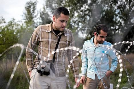 Damaskoksesta kotoisin olevat syyrialaisveljekset Jalal (vas.) ja Hassan tarkkailivat Unkarin rakentamaa aitaa Röszken raja-aseman Serbian puolella keskiviikkona. Lauantaina Unkari ilmoitti saaneensa valmiiksi piikkilankaesteen myös Kroatian-vastaiselle rajalleen.