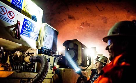 Länsimetron louhinta-alueella räjähteet valmistetaan panostusalustalla. Louhintavalvoja Timo Räty osoittaa taskulampulla panostusalustan mittareita projektipäällikkö Tero Palmun seuratessa vieressä.