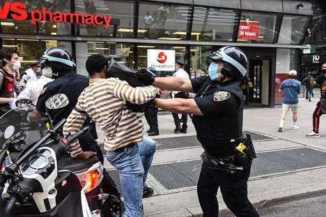 Mielenosoittajat ja poliisi ottavat yhteen Minneapolisissa ja kansalliskaarti saapui paikalle perjantaina iltapäivällä. Kuva torstailta New Yorkista.
