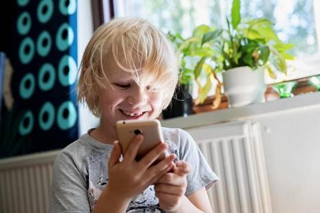 """Ensimmäisen luokan aloittava Aarne Pekkinen, 6, sai ensipuhelimensa jo kesä loman alussa, sillä kaikilla esikoulukavereilla oli sellainen. Puhelimeksi valikoitui kullanvärinen Honor 6A. """"Puhelimen saaminen tuntui hassulta, koska en ollut tottunut siihen. Olen yrittänyt soittaa sillä, mutta kukaan ei yleensä vastaa. Sitten pelaan Drive Aheadia ja Pokemonia ja kirjoitan Whatsappissa viestejä melkein kaikille. Parasta on laittaa puhelin päälle"""", Aarne sanoo."""