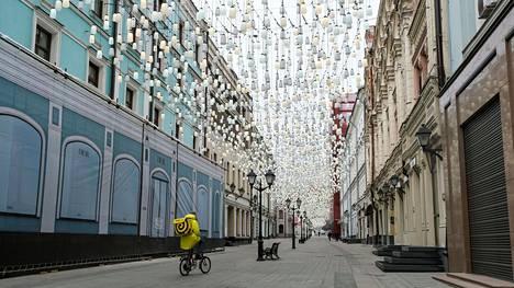 Ruokalähetti ajoi pyörällä tyhjällä kävelykadulla Moskovan keskustassa maanantaina.
