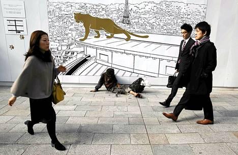 Koditon torkkui Ginza-ostosalueen jalkakäytävällä Tokiossa sunnuntaina. Japanin taloudessa ei mene hyvin, sillä maa luisui yllättäen taantumaan vuoden kolmannella neljänneksellä.