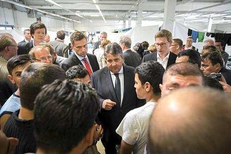 Saksan sosiaalidemokraattisen puolueen SPD:n johtaja Sigmar Gabriel (kesk.) puhui syyrialaisten ja afganistanilaisten kanssa vastaanottokeskuksessa Heidenaussa maanantaina.