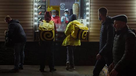 Yandexin lähetit odottavat tilausten valmistumista Moskovan keskustassa sijaitsevalla kioskilla.