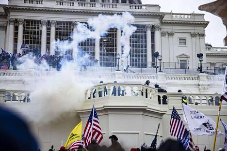 Trumpin kannattajia savun seassa kongressitalon ulkopuolella.