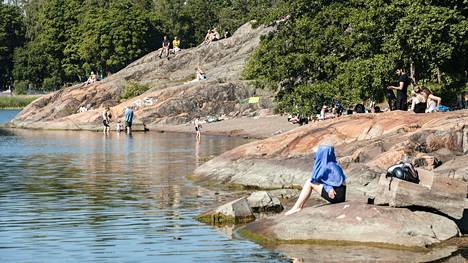 Ihmiset viettivät juhannuspäivää merenrannalla Helsingin Lapinlahdessa.