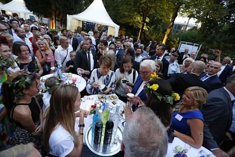 Saksan liittopresidentti Frank-Walter Steinmeir, hänen puolisonsa Elke Büdenbender ja Suomen opetusministeri Li Andersson maistelevat suomalaisia suolapaloja Steinmeierin Bellevuen linnan puutarhassa kansalaisjuhlan Suomen-osastolla.
