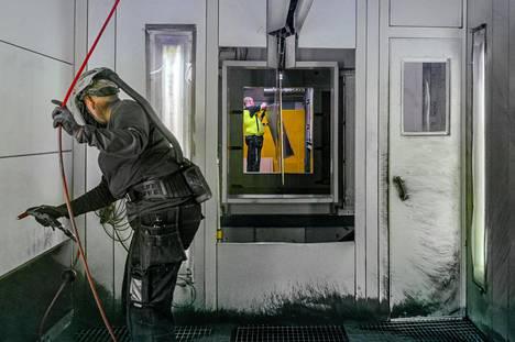 Katja Ratilainen puhdistaa maalauskammiota Finelcompin tehtaalla Outokummussa. Yrityksen on ollut vaikea löytää uusia työntekijöitä Pohjois-Karlan runsaasta työttömyydestä huolimatta.