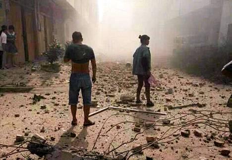 Ihmiset kummastelivat voimakkaiden räjähdysten jälkiä Liuzhoun kaupungissa.