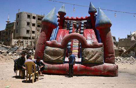 Raunioiden keskelle pystytetty pomppulinna näyttää myös vähän kärsineeltä Douman alueella Syyrian pääkaupungissa Damaskoksessa, jossa vietettiin maanantaina Eid-juhlaa.